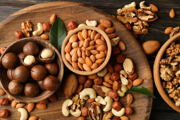 Tray with bowls with different nuts on wooden background