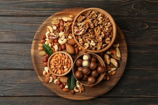 Tray with bowls with different nuts on wooden