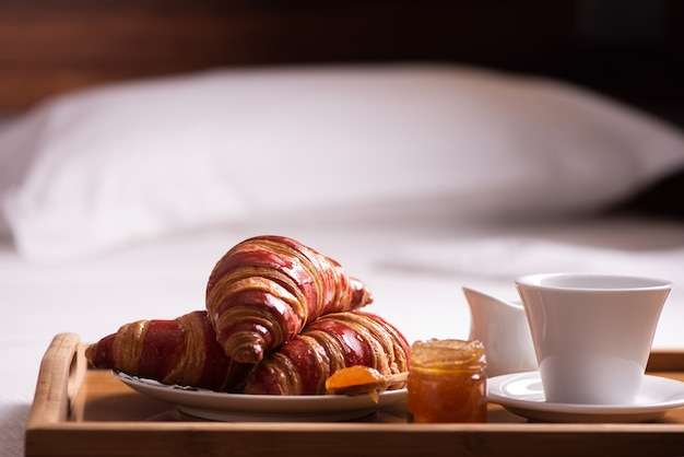 Tray with breakfast on a bed in hotel room