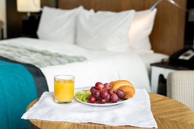現代的な豪華なホテルの部屋の1つの中のベッドに対してカメラの前の小さな木製のテーブルの上に立っている朝食とトレイ