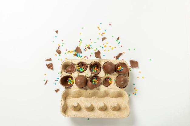 Поднос с разбитыми пасхальными шоколадными яйцами и разноцветными украшениями из сладких конфет на свету