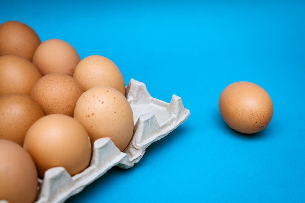 Tray with brown eggs on a blue background, one egg is separate.