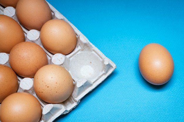 Tray with brown eggs on a blue background, one egg is separate