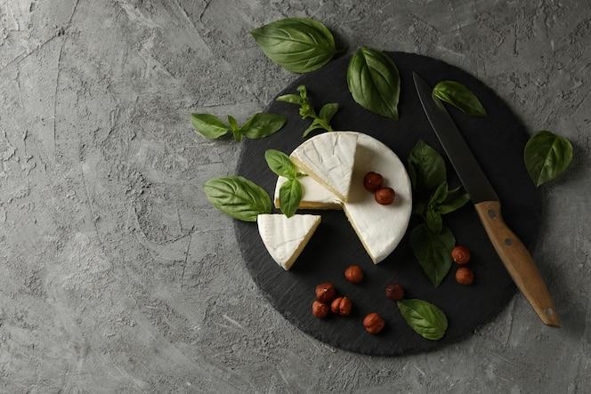 vassoio con camembert, nocciola, basilico e coltello su sfondo grigio