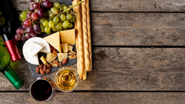 Tray with cheese and grapes beside wine bottle