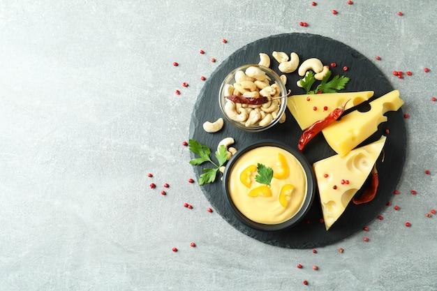 グレーのテクスチャードテーブルにチーズソースと材料を入れたトレイ