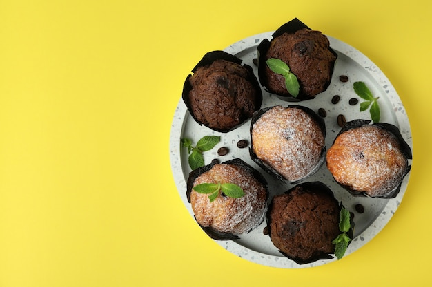 Tray with chocolate muffins on yellow background.