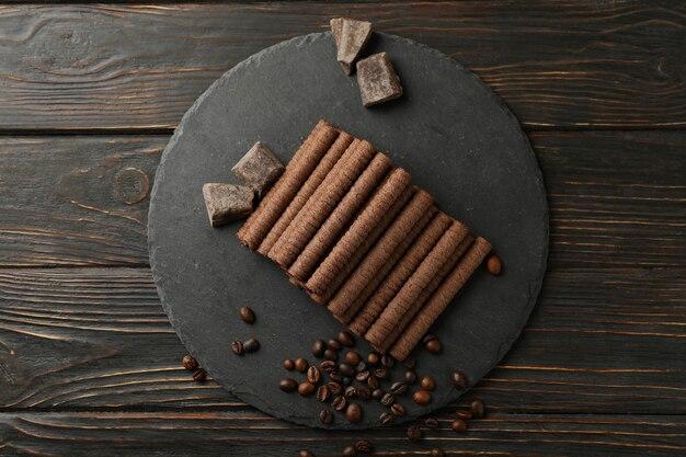 Поднос с шоколадными вафельными трубочками, кофейными зернами и шоколадом на деревянном