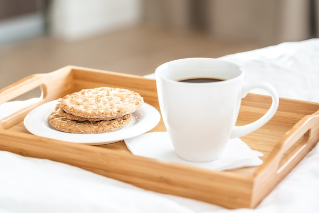 Tray with coffee and crackers breakfast on a bed