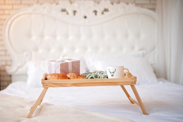 커피, 크루아상 및 침대에 선물이 담긴 트레이