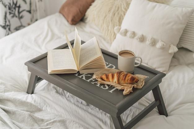 クロワッサン、一杯のコーヒーと白いきれいなベッドの上の本でトレイ。