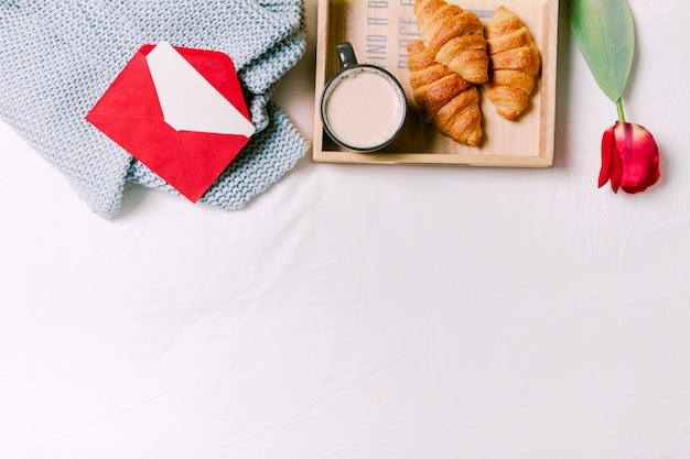 Tray with croissants and cup of milk on bed