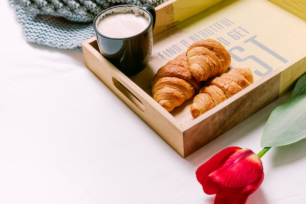 Tray with croissants and cup of milk on light bed