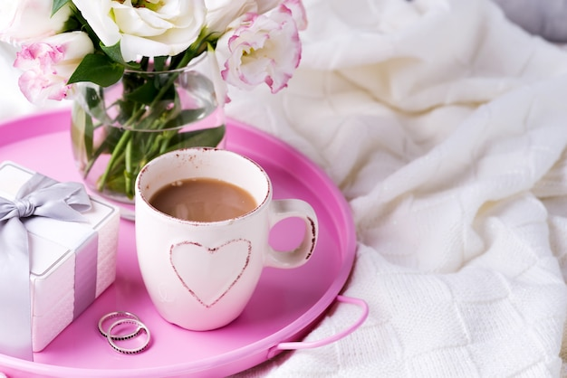 A tray with a cup of coffee, gift box, flowers and rings on the bed. valentine's day wedding offer