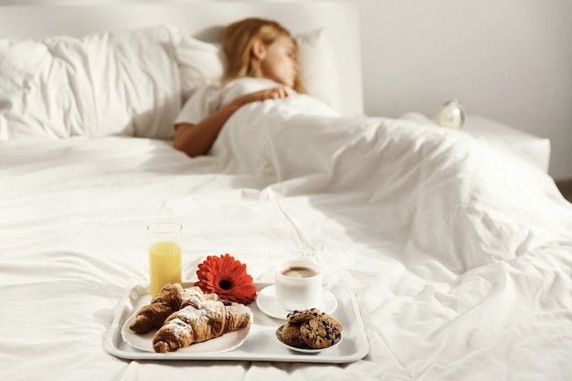 Tray with cup of coffee, glass of juice, red flower, croissants and cookies stands on white bed while woman sleeps
