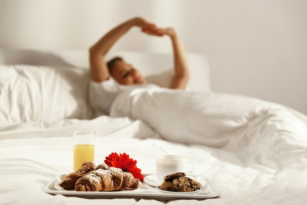 Tray with cup of coffee, glass of juice, red flower, croissants and cookies stands on white bed while woman wakes up