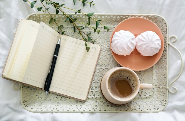 Tray with cup of coffee, tasty zephyr and notebook on bed