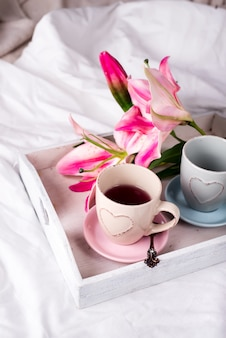 Tray with cup of hot tea in the bed,