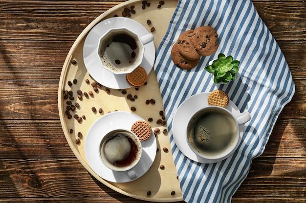 Поднос с чашками вкусного ароматного кофе на деревянном столе, вид сверху