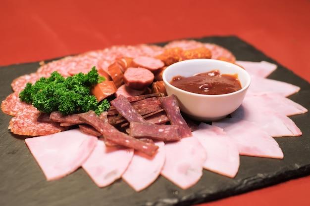 Поднос с вкусными ломтиками салями салат из рубленой ветчины и колбасы
