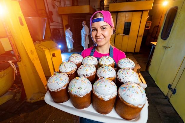 工業用ベーカリーの背景のテクスチャでイースターケーキとトレイ。女性は新鮮な裏付けのあるトレイを持っています。