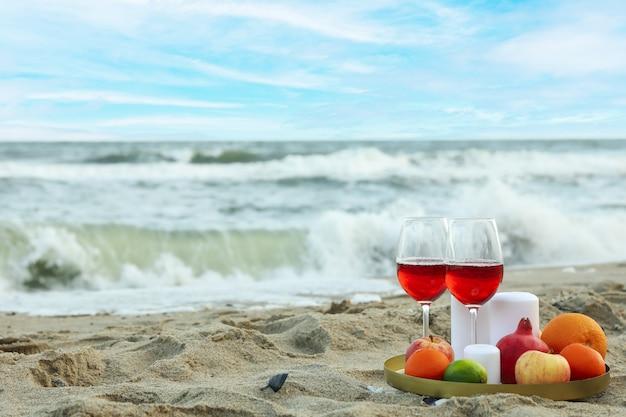 砂浜のビーチでワイン、フルーツ、キャンドルのグラスとトレイ