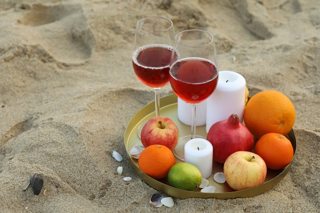 Tray with glasses of wine, fruits and candles on sandy sea beach
