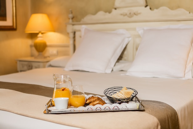 Tray with healthy breakfast food on bed