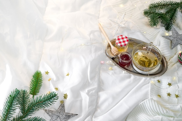 Tray with honey and a cup of hot tea in the bed, lazy morning, warm winter mood