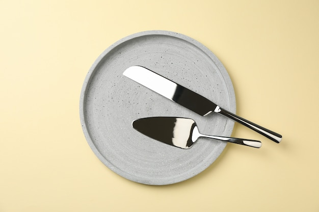 Tray with knife and pizza shovel on beige background, top view