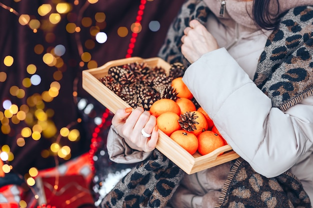 Поднос с мандаринами и шишками на открытом воздухе.