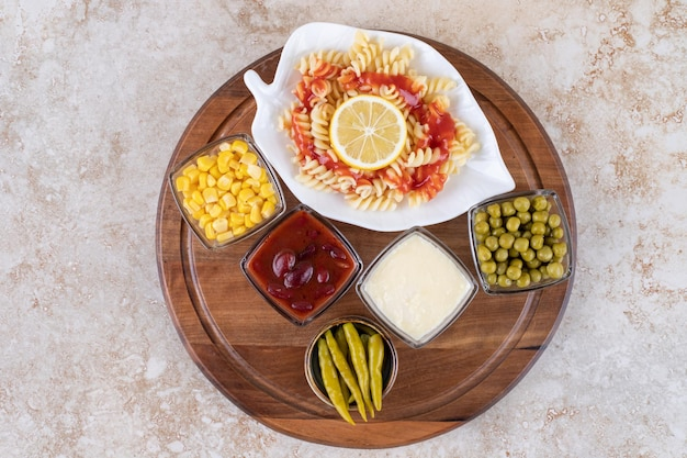 Tray with pasta serving and bowls of toppings and dressings on marble surface.