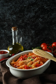 Tray with pasta with tomato sauce against black smokey isolated background