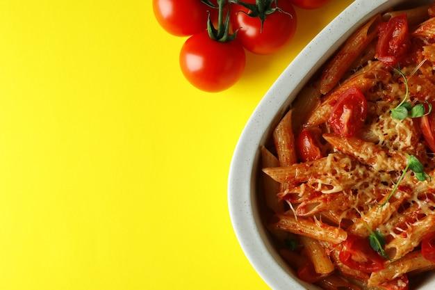 토마토 소스와 노란색 배경에 재료와 파스타, 상위 뷰 트레이