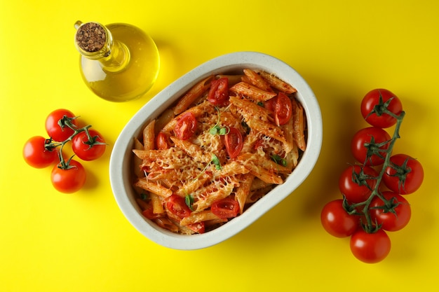 Tray with pasta with tomato sauce and ingredients on yellow isolated background, top view