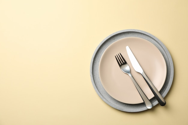 Tray with plate, fork and knife on beige background, top view