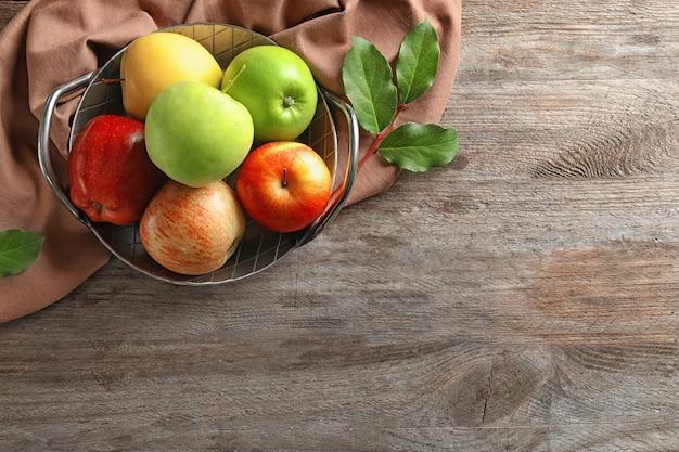 Поднос со спелыми сочными яблоками на деревянном столе, вид сверху