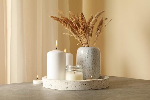향기로운 양초와 회색 테이블에 리드 트레이