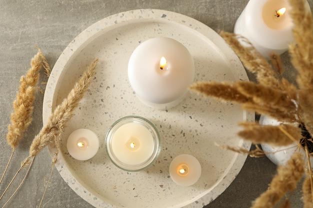 香りのキャンドルと灰色のテーブルの上の葦のトレイ