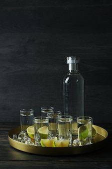 Tray with shots and bottle of vodka on wooden