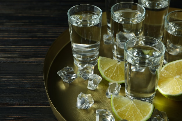 Tray with shots, lime slices and ice cubes on wooden