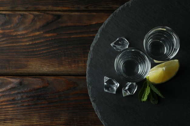 Tray with shots of vodka on wooden table