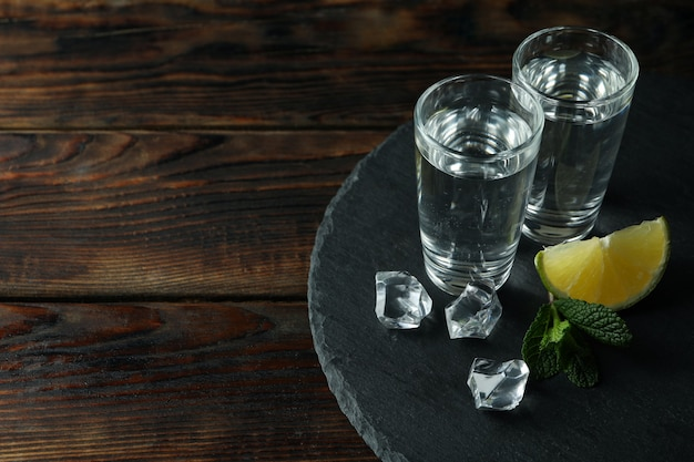 Tray with shots of vodka on wooden