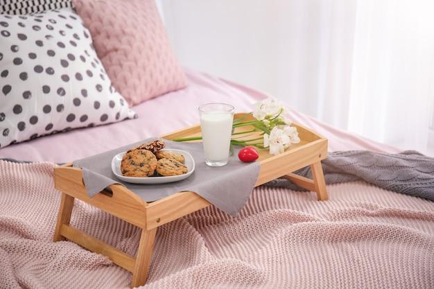 맛있는 아침 식사와 침대에 꽃 트레이