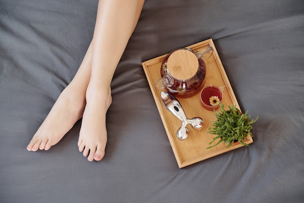 Tray with teapot and face roller on bed next to beautiful legs of young woman, view from above