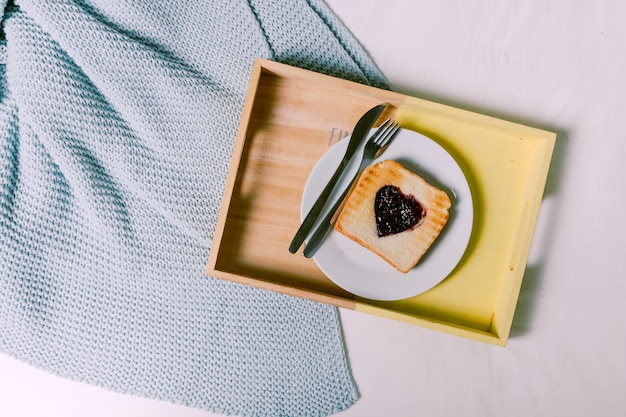 Tray with toast with jam in heart shape on bed
