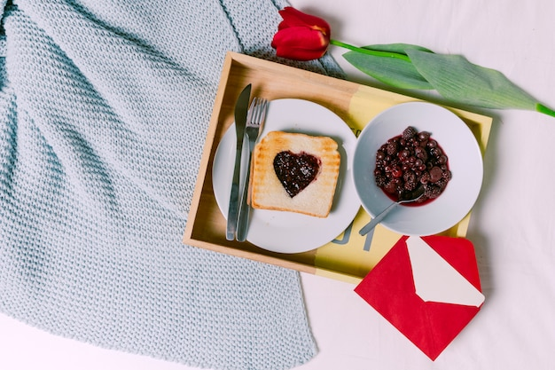 Tray with toast with jam in heart shape and berries