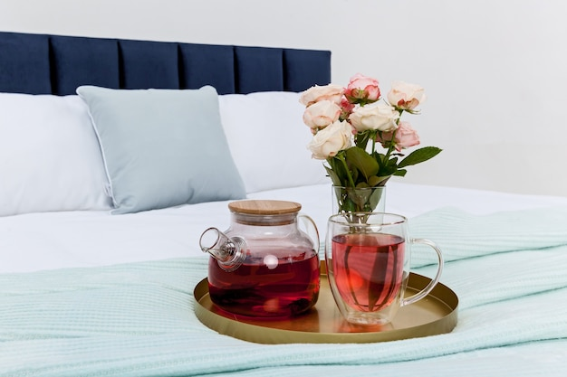A tray with a transparent teapot a mug and a vase with roses are on the bed in the bedroom