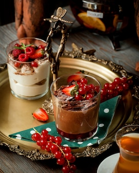 A tray with two glasses of tiramisu and chocolate pudding garnished with berries