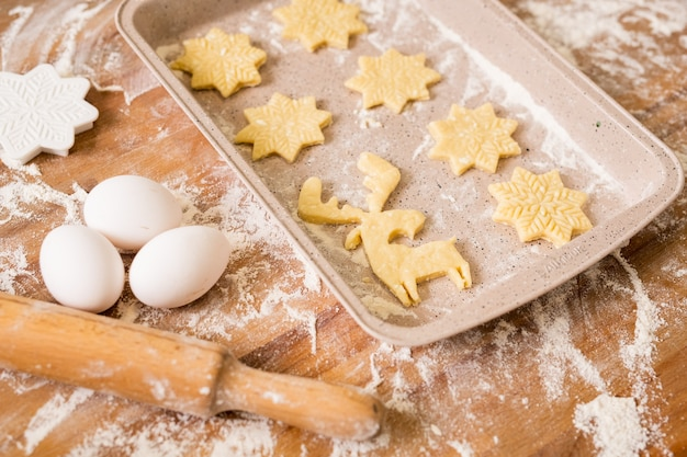 Tray with two rows of raw christmas cookies with three eggs, rolling pin, flour and cutters near by on table